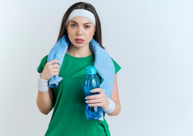 Zuversichtlich junge sportliche frau, die stirnband und armbänder mit handtuch um den hals hält wasserflasche suchen