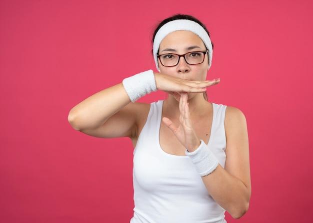 Zuversichtlich junge sportliche frau in der optischen brille, die stirnband und armbänder trägt, gestikuliert auszeitzeichen lokalisiert auf rosa wand
