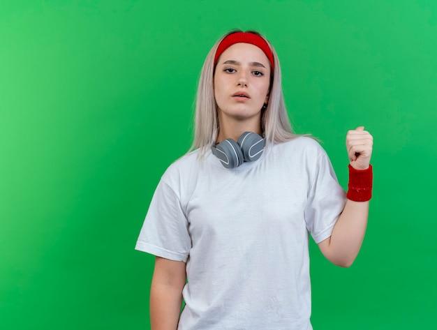 Zuversichtlich junge sportliche frau mit hosenträgern, die stirnband und armbänder mit kopfhörern am hals tragen, zeigen zurück lokalisiert auf grüner wand