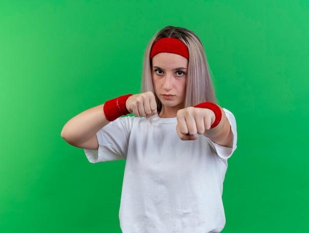 Zuversichtlich junge sportliche frau mit hosenträgern, die stirnband und armbänder tragen, hält fäuste bereit, isoliert auf grüner wand zu schlagen