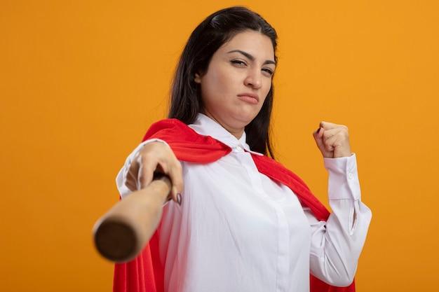 Zuversichtlich junge superfrau, die baseballschläger nach vorne ausdehnt und die auf der orangefarbenen wand isolierte vordere geballte faust betrachtet