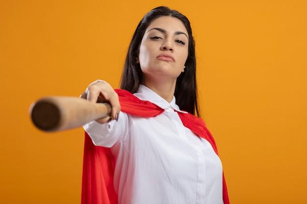 Zuversichtlich junge superfrau, die baseballschläger nach vorne ausdehnt und front betrachtet, die auf orange wand lokalisiert ist