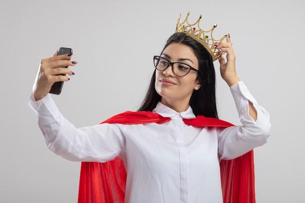 Zuversichtlich junge superfrau, die brille und krone berührt krone trägt selfie auf weißer wand isoliert
