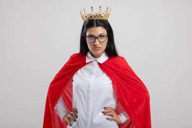 Zuversichtlich junge superfrau, die brille und krone trägt, die front hält hände auf taille lokalisiert auf weißer wand hält