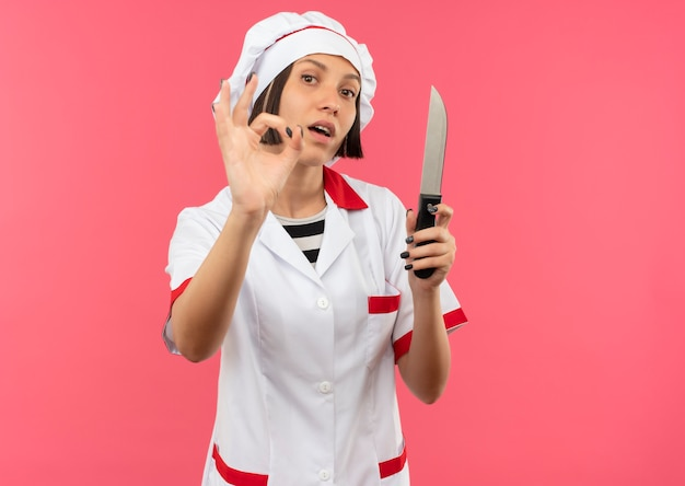 Zuversichtlich junge weibliche köchin in der kochuniform, die messer hält und ok-zeichen tut, das auf rosa mit kopienraum lokalisiert wird