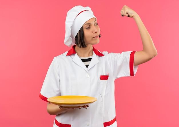 Zuversichtlich junge weibliche köchin in der kochuniform, die starken halteteller gestikuliert und ihren arm lokalisiert auf rosa betrachtet