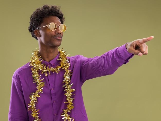 Zuversichtlich junger afroamerikanischer mann, der brille mit lametta-girlande um den hals trägt, der auf seite lokalisiert auf olivgrünem hintergrund schaut und zeigt