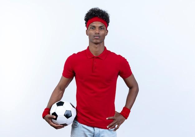 Zuversichtlich junger afroamerikanischer sportlicher mann, der haarband und armband hält ball hält und hand auf hüfte lokalisiert auf weißem hintergrund setzt