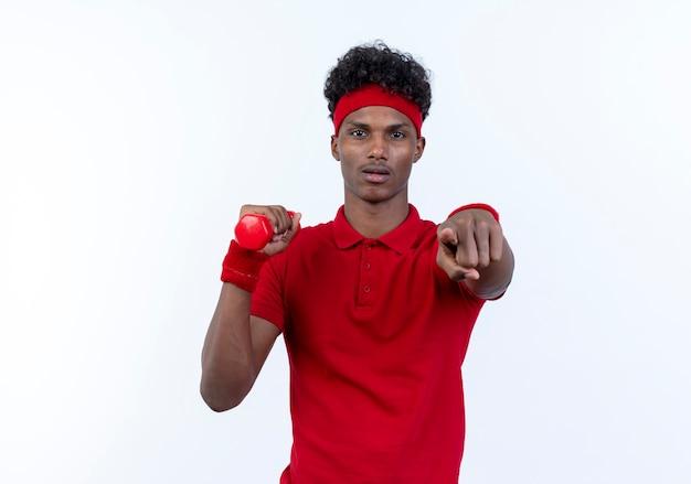 Zuversichtlich junger afroamerikanischer sportlicher mann, der haarband und armband hält hantel hält und sie geste lokalisiert auf weißem hintergrund zeigt