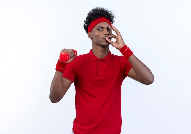 Zuversichtlich junger afroamerikanischer sportlicher mann, der haarband und armband hält hantel um schulter hält und köstliche geste lokalisiert auf weißem hintergrund zeigt