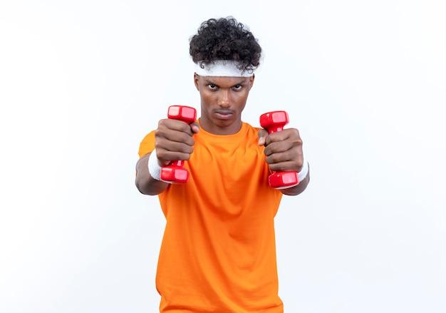 Zuversichtlich junger afroamerikanischer sportlicher mann, der stirnband und armband trägt, die hanteln heraushalten