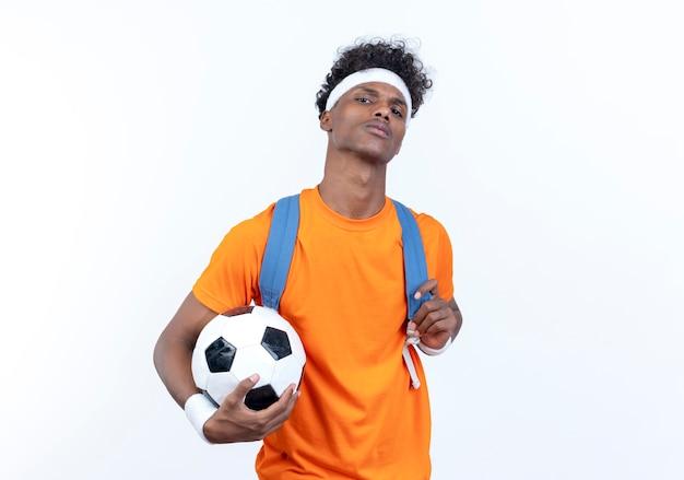 Zuversichtlich junger afroamerikanischer sportlicher mann, der stirnband und armband und rückentasche hält ball lokalisiert auf weißem hintergrund trägt
