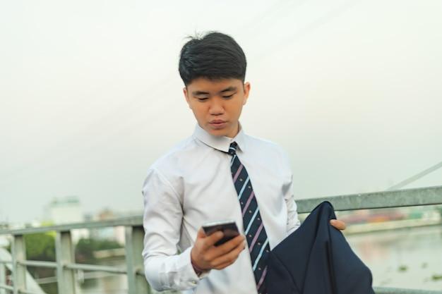 Zuversichtlich junger asiatischer geschäftsmann, der seine anzugjacke hält, während er sein telefon überprüft