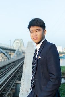 Zuversichtlich junger asiatischer mann in einem anzug, der sich auf eine brücke stützt