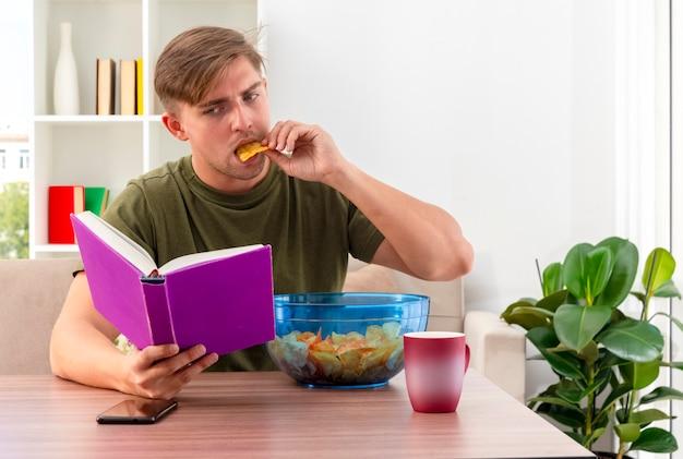 Zuversichtlich junger blonder gutaussehender mann sitzt am tisch mit schüssel chips tasse und telefon hält und schaut auf buch, das chips im wohnzimmer isst