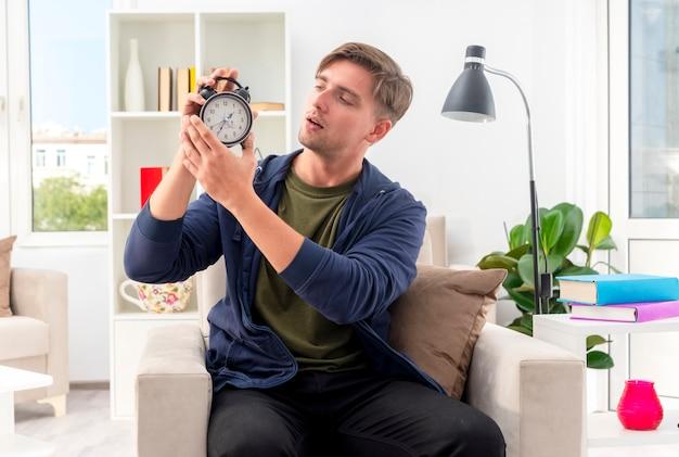 Zuversichtlich junger blonder gutaussehender mann sitzt auf sessel, der wecker im wohnzimmer hält und schaut