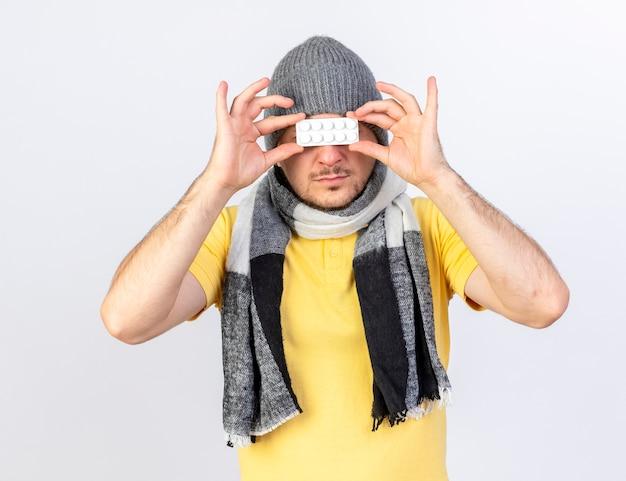 Zuversichtlich junger blonder kranker mann, der wintermütze und schal trägt, hält packung der medizinischen pillen vor den augen lokalisiert auf weißer wand