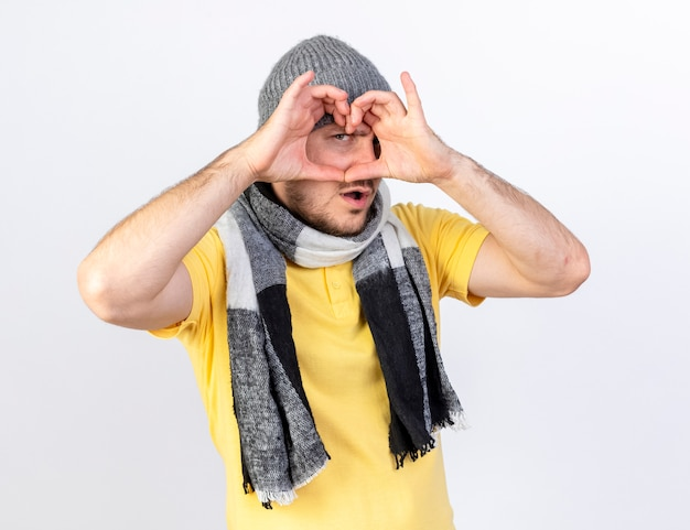 Zuversichtlich junger blonder kranker mann, der wintermütze und schalgesten trägt und vorne durch herzzeichen lokalisiert auf weißer wand schaut