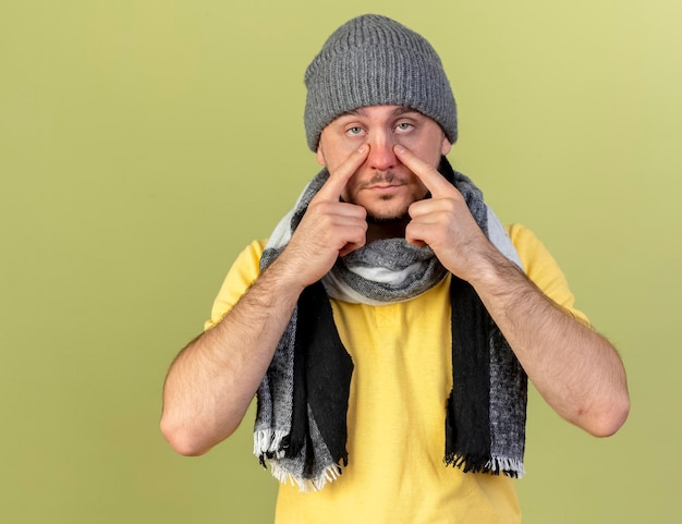 Zuversichtlich junger blonder kranker slawischer mann, der wintermütze und schal trägt