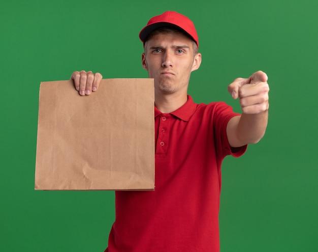 Zuversichtlich junger blonder lieferjunge hält papierpaket und punkte lokalisiert auf grüner wand mit kopienraum
