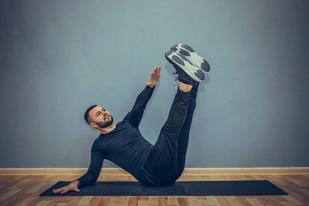 Zuversichtlich junger fitnessmann, der auf einer fitnessmatte drinnen, über graue wand ausübt