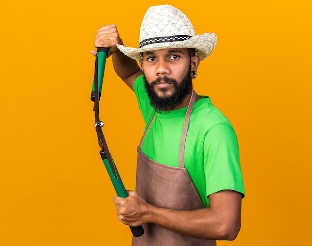 Zuversichtlich junger gärtner afroamerikanischer mann mit gartenhut mit schermaschine