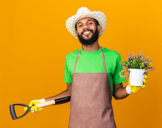Zuversichtlich junger gärtner afroamerikanischer mann mit gartenhut und handschuhen, der spaten mit blume im blumentopf hält