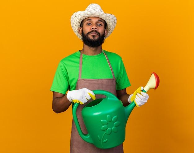 Zuversichtlich junger gärtner afroamerikanischer mann mit gartenhut und handschuhen, die gießkanne isoliert auf oranger wand halten