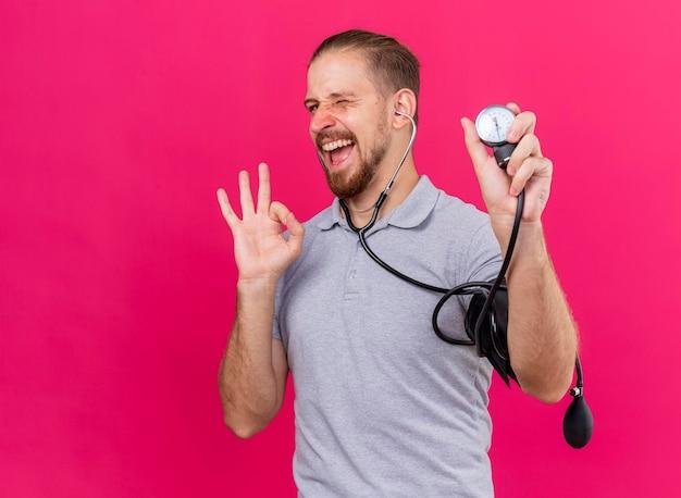 Zuversichtlich junger gutaussehender slawischer kranker mann, der stethoskop trägt, das seinen druck mit blutdruckmessgerät misst, das vorne zwinkert und ok singt auf rosa wand mit kopienraum