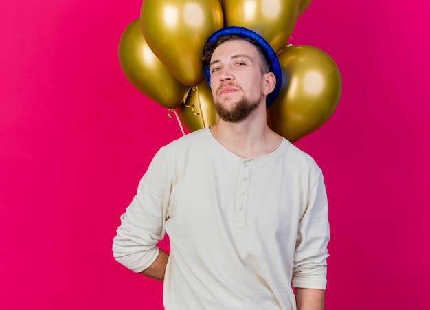 Zuversichtlich junger gutaussehender slawischer party-typ, der partyhut hält, der ballons hinter seinem rücken hält und kamera lokalisiert auf purpurrotem hintergrund mit kopienraum betrachtet
