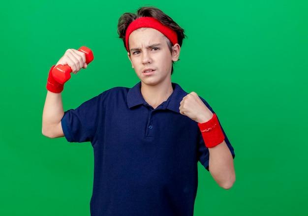 Zuversichtlich junger gutaussehender sportlicher junge, der stirnband und armbänder mit zahnspangen trägt, die die hantel ballende faust anheben, die vorne auf grüner wand mit kopienraum lokalisiert betrachtet