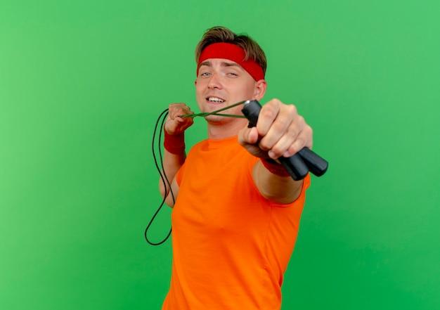 Zuversichtlich junger gutaussehender sportlicher mann, der stirnband und armbänder trägt, die springseil in richtung kamera ziehen und strecken, die auf grün mit kopienraum isoliert wird
