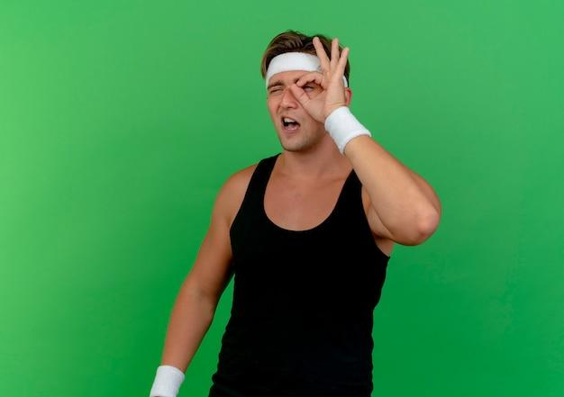 Zuversichtlich junger gutaussehender sportlicher mann, der stirnband und armbänder tut, die blickgestik lokalisiert auf grün mit kopienraum tun