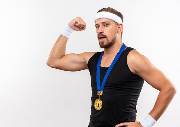 Zuversichtlich junger gutaussehender sportlicher mann mit stirnband und armbändern, der stark mit der hand auf der taille gestikuliert, isoliert auf weißer wand mit kopierraum
