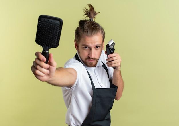 Zuversichtlich junger hübscher friseur, der kamm ausstreckt und haarschneidemaschine lokalisiert auf olivgrün mit kopienraum hält
