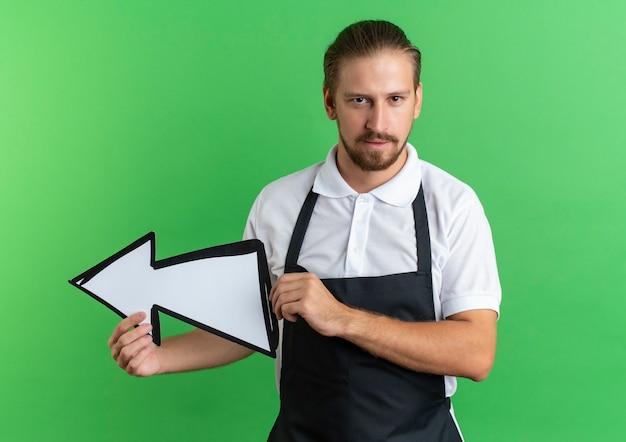 Zuversichtlich junger hübscher friseur, der uniform hält, die pfeilmarkierung hält, die auf seite zeigt, die auf grün isoliert ist