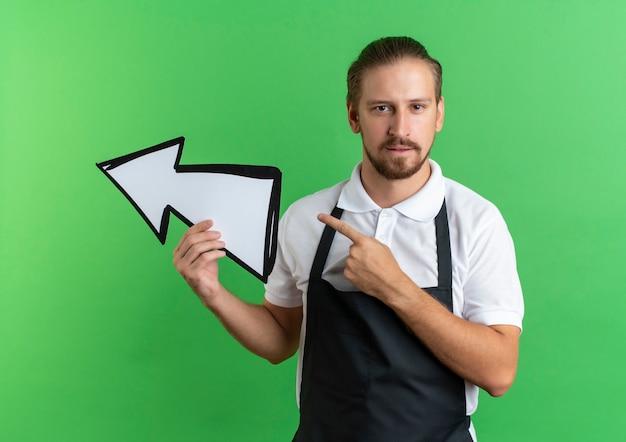 Zuversichtlich junger hübscher friseur, der uniform hält, die pfeilmarkierung hält und zur seite zeigt, die auf grün lokalisiert wird
