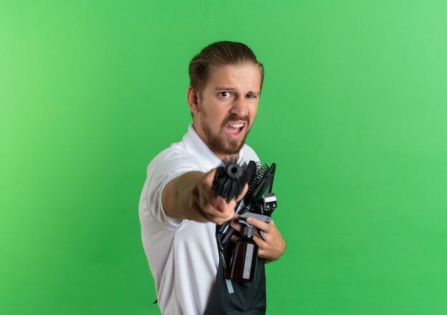 Zuversichtlich junger hübscher friseur, der uniform hält kämme, sprühflasche, haarschneidemaschine und ausgestreckten kamm in richtung kamera auf grün mit kopierraum isoliert
