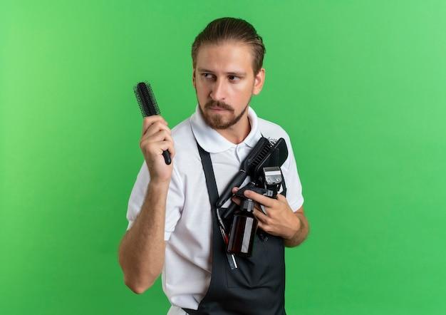Zuversichtlich junger hübscher friseur, der uniform hält kämme, sprühflasche, haarschneidemaschinen, die seite lokal auf grün mit kopienraum betrachten