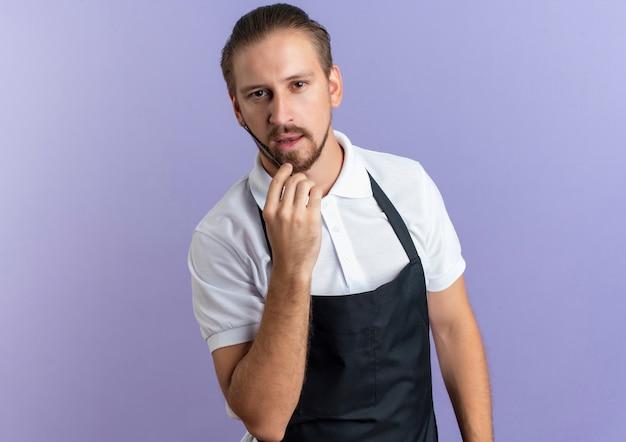 Zuversichtlich junger hübscher friseur, der uniform trägt, die seinen bart kämmt, isoliert auf purpur mit kopienraum