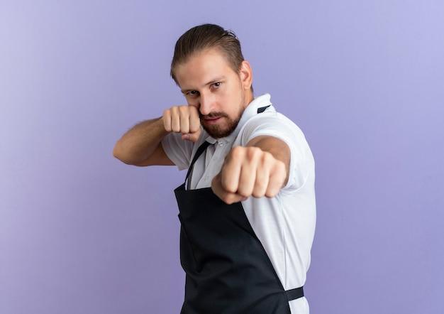 Zuversichtlich junger hübscher friseur, der uniform tut, die boxgeste tut, lokalisiert auf purpur mit kopienraum