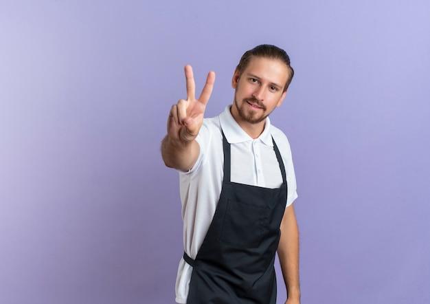 Zuversichtlich junger hübscher friseur, der uniform tut, die friedenszeichen lokalisiert auf purpur mit kopienraum tut
