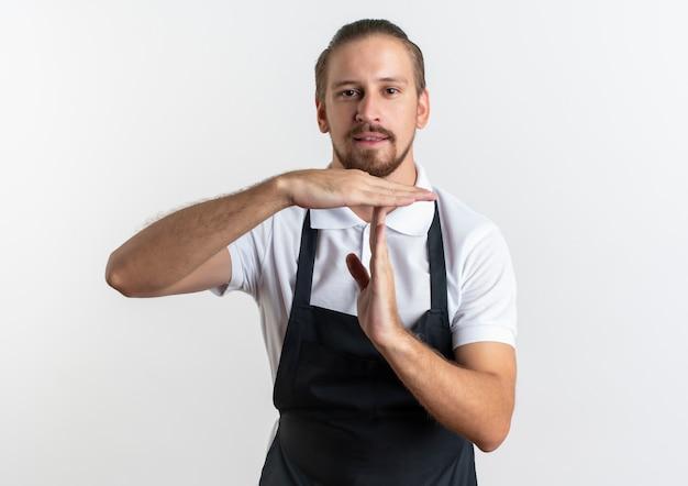 Zuversichtlich junger hübscher friseur, der uniform tut, die zeitüberschreitungsgeste tut, lokalisiert auf weiß mit kopienraum