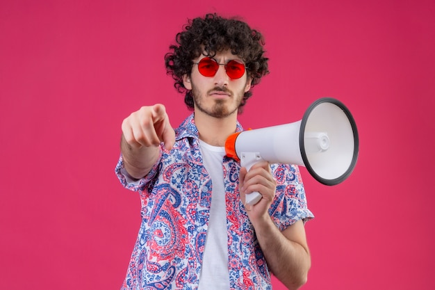 Zuversichtlich junger hübscher gelockter reisender mann, der sonnenbrille hält lautsprecher hält und auf isolierten rosa raum mit kopienraum zeigt