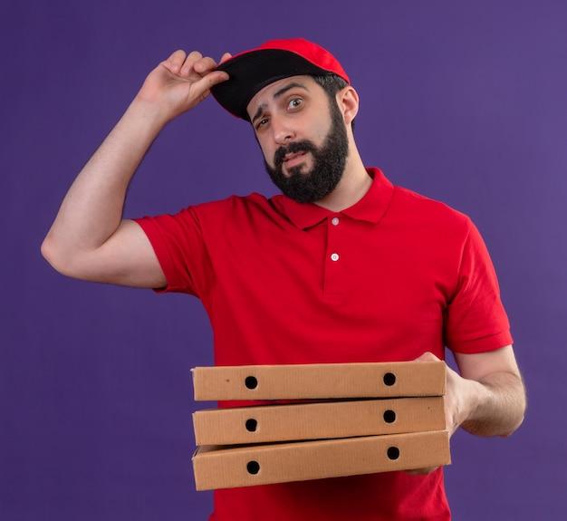 Zuversichtlich junger hübscher kaukasischer lieferbote, der rote uniform und kappe hält, die pizzaschachteln und seine kappe lokalisiert auf lila hält