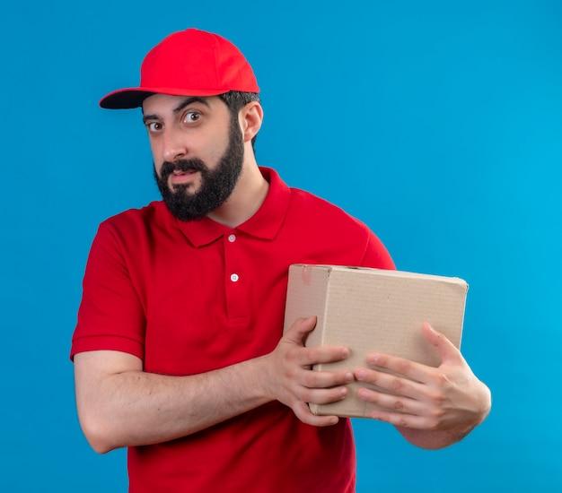 Zuversichtlich junger hübscher kaukasischer lieferbote, der rote uniform und kappe hält kartonbox auf blau isoliert trägt