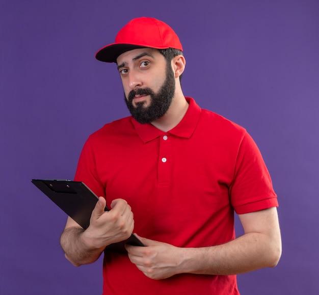 Zuversichtlich junger hübscher kaukasischer lieferbote, der rote uniform und kappe hält zwischenablage lokalisiert auf lila trägt