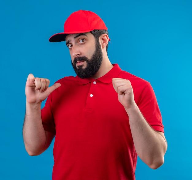 Zuversichtlich junger hübscher kaukasischer lieferbote, der rote uniform und kappe trägt, die auf blau lokalisiert auf sich zeigen
