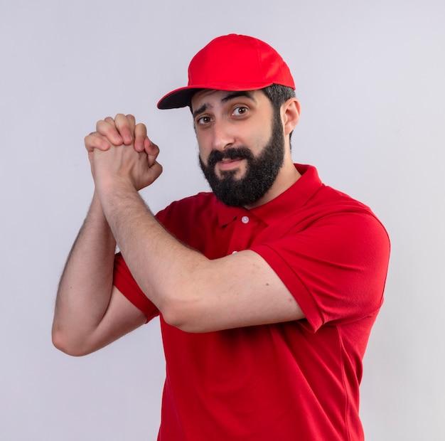 Zuversichtlich junger hübscher kaukasischer lieferbote, der rote uniform und kappe trägt, die seine hände zusammen auf weiß isoliert halten