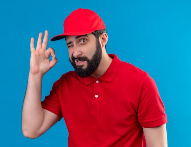 Zuversichtlich junger hübscher kaukasischer lieferbote, der rote uniform und mütze zwinkert und ok-zeichen tut, das auf blau isoliert wird